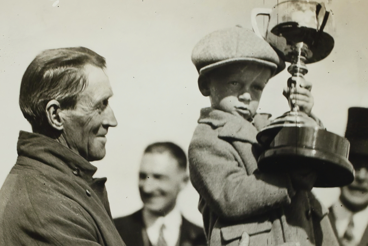 An old photograph of a man holding a boy as he holds onto a large trophy
