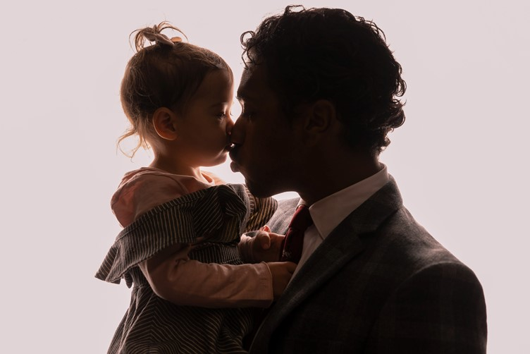 A father kissing his young daughter